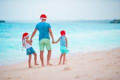 Τα μικρά κορίτσια και ο νέος μπαμπάς στα καπέλα Santa απολαμβάνουν τις διακοπές Χριστουγέννων Στοκ φωτογραφίες με δικαίωμα ελεύθερης χρήσης