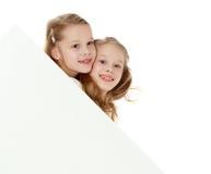Τα μικρά κορίτσια κοιτάζουν έξω από πίσω από το έμβλημα στοκ εικόνες με δικαίωμα ελεύθερης χρήσης