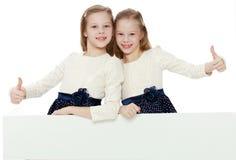 Τα μικρά κορίτσια κοιτάζουν έξω από πίσω από το έμβλημα στοκ φωτογραφία με δικαίωμα ελεύθερης χρήσης