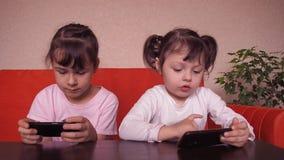 Τα μικρά κορίτσια παίζουν με ένα κινητό τηλέφωνο απόθεμα βίντεο