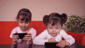 Τα μικρά κορίτσια παίζουν με ένα κινητό τηλέφωνο φιλμ μικρού μήκους