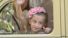 Τα μικρά κορίτσια παίζουν στην μπροστινή συνεδρίαση του αναδρομικού αυτοκινήτου απόθεμα βίντεο