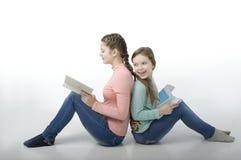 Τα μικρά κορίτσια που διαβάζονται τα βιβλία πλάτη με πλάτη στο λευκό Στοκ εικόνες με δικαίωμα ελεύθερης χρήσης