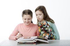 Τα μικρά κορίτσια που διαβάζονται τα βιβλία στον πίνακα στο λευκό Στοκ Φωτογραφία