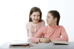 Τα μικρά κορίτσια που διαβάζονται τα βιβλία στον πίνακα στο λευκό Στοκ εικόνα με δικαίωμα ελεύθερης χρήσης