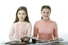 Τα μικρά κορίτσια που διαβάζονται τα βιβλία στον πίνακα στο λευκό Στοκ φωτογραφία με δικαίωμα ελεύθερης χρήσης