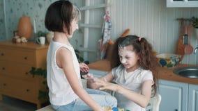 Τα μικρά κορίτσια που ρίχνουν το αλεύρι το ένα στο άλλο, έχουν το χρόνο διασκέδασης στην κουζίνα, σε αργή κίνηση απόθεμα βίντεο