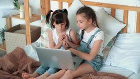 Τα μικρά κορίτσια προσέχουν κάτι στο lap-top και το συζητούν συναισθηματικά, σε αργή κίνηση απόθεμα βίντεο