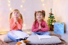 Τα μικρά κορίτσια σε αναμονή για τις νέες διακοπές έτους ` s κάνουν τις επιθυμίες Στοκ εικόνα με δικαίωμα ελεύθερης χρήσης