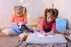 Τα μικρά κορίτσια σε αναμονή για τις νέες διακοπές έτους ` s κάνουν τις επιθυμίες Στοκ εικόνες με δικαίωμα ελεύθερης χρήσης
