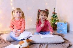 Τα μικρά κορίτσια σε αναμονή για τις νέες διακοπές έτους ` s κάνουν τις επιθυμίες Στοκ Εικόνες