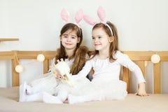 Τα μικρά κορίτσια στα αυτιά κουνελιών κάθονται στον καναπέ με τα καλάθια Πάσχας Στοκ φωτογραφία με δικαίωμα ελεύθερης χρήσης
