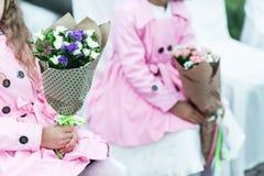 Τα μικρά κορίτσια στα ρόδινα παλτά κάθονται στις άσπρες καρέκλες κρατώντας το bouqu Στοκ φωτογραφίες με δικαίωμα ελεύθερης χρήσης