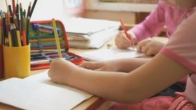 Τα μικρά κορίτσια σύρουν τις εικόνες στο copybook φιλμ μικρού μήκους