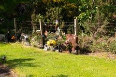 Τα μικρά μνημεία στα παιδιά στην πλευρά οι σκιασμένες περιοχές του νεκροταφείου στοκ εικόνες