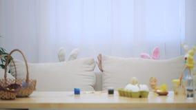 Τα μικρά παίζοντας παιδιά με τα αυτιά λαγουδάκι στα κεφάλια τους κρύβουν κάτω από τον άνετο κυματισμό καναπέδων Το χαριτωμένο αγό απόθεμα βίντεο