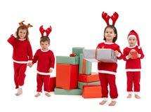 Τα μικρά παιδιά στα κόκκινα Χριστούγεννα ντύνουν με το παρόν στοκ φωτογραφία με δικαίωμα ελεύθερης χρήσης