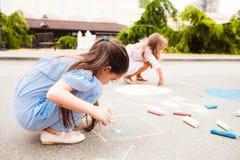 Τα μικρά παιδιά σύρουν στην κιμωλία μεταξύ της οδού πόλεων στοκ εικόνα