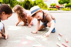 Τα μικρά παιδιά σύρουν στην κιμωλία μεταξύ της οδού πόλεων στοκ εικόνες