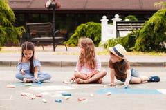 Τα μικρά παιδιά σύρουν στην κιμωλία μεταξύ της οδού πόλεων στοκ εικόνα με δικαίωμα ελεύθερης χρήσης