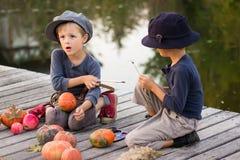 Τα μικρά παιδιά χρωματίζουν τις μικρές κολοκύθες αποκριών Στοκ Εικόνα