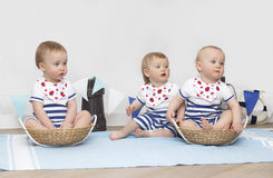 Τα μικρά παιδιά κάθονται σε ένα άσπρο υπόβαθρο, χαμόγελο μπλε θαλάσσιο άνευ ραφής θέμα θάλασσας Στοκ φωτογραφία με δικαίωμα ελεύθερης χρήσης