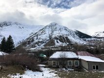 Τα μικρά σπίτια πετρών, κτήρια στο χωριό σε έναν όμορφο κρύο χειμώνα βουνών προσφεύγουν με την υδρονέφωση και το χιόνι αιχμών υψη στοκ εικόνα με δικαίωμα ελεύθερης χρήσης