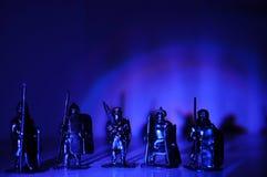 Τα μικροσκοπικά ειδώλια αναμνηστικών ιπποτών πολεμιστών λεγεωναρίων δίνουν - καμένος, ελαφρύ σκοτεινό υπόβαθρο αψίδων Στοκ Εικόνα