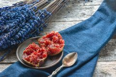 Τα μισά των ώριμων σύκων με ένα κουτάλι σε ένα lavender υπόβαθρο και ένα όμορφο φθινόπωρο φεύγουν Κινηματογράφηση σε πρώτο πλάνο  Στοκ εικόνα με δικαίωμα ελεύθερης χρήσης