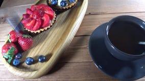 Τα μούρα χύνονται σε ένα ξύλινο πιάτο με ένα επιδόρπιο, ο σερβιτόρος εξυπηρετεί το επιδόρπιο απόθεμα βίντεο