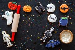 Τα μπισκότα μελοψωμάτων αποκριών μαγείρων κτυπούν, σκελετός, γλυκά φαντασμάτων που κυλούν πλησίον την καρφίτσα στη μαύρη τοπ άποψ Στοκ Εικόνες
