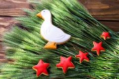Τα μπισκότα μελοψωμάτων διαμόρφωσαν την πάπια και τα κόκκινα αστέρια με το αυτί του σίτου σε ένα ξύλινο υπόβαθρο πεδίο βάθους ρηχ Στοκ Εικόνες