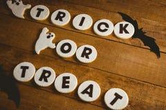 Τα μπισκότα με το τέχνασμα ή μεταχειρίζονται το κείμενο από τις απόκοσμες διακοσμήσεις στον ξύλινο πίνακα Στοκ Φωτογραφία