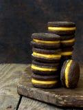 Τα μπισκότα σάντουιτς σοκολάτας με την πορτοκαλιά κρέμα συσσώρευσαν την υψηλή πλάτη Στοκ Εικόνες