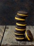 Τα μπισκότα σάντουιτς σοκολάτας με την πορτοκαλιά κρέμα συσσώρευσαν την υψηλή πλάτη Στοκ Φωτογραφίες
