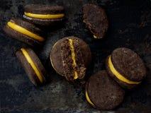 Τα μπισκότα σάντουιτς σοκολάτας με την πορτοκαλιά κρέμα συσσώρευσαν την υψηλή πλάτη Στοκ εικόνα με δικαίωμα ελεύθερης χρήσης
