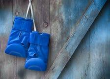 Τα μπλε εγκιβωτίζοντας γάντια κρεμούν σε ένα καρφί σε έναν ξύλινο shabby τοίχο Στοκ Εικόνες