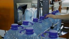 Τα μπουκάλια με το νερό κινούνται κατά μήκος της ζώνης μεταφορέων ενώ ο υπάλληλος ρυθμίζει τις λαβές στα καπάκια απόθεμα βίντεο