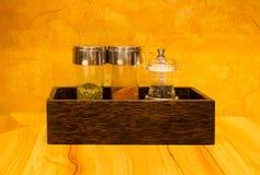 Τα μπουκάλια καρυκευμάτων μέσα στο ξύλινο κιβώτιο στον πίνακα Στοκ Εικόνες