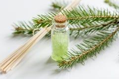 Τα μπουκάλια του άλατος και του έλατου θάλασσας διακλαδίζονται για aromatherapy και τη SPA στο άσπρο επιτραπέζιο υπόβαθρο Στοκ εικόνα με δικαίωμα ελεύθερης χρήσης