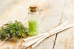 Τα μπουκάλια του άλατος και του έλατου θάλασσας διακλαδίζονται για aromatherapy και τη SPA στο άσπρο επιτραπέζιο υπόβαθρο Στοκ Εικόνα