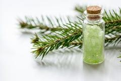 Τα μπουκάλια του άλατος και του έλατου θάλασσας διακλαδίζονται για aromatherapy και τη SPA στο άσπρο επιτραπέζιο υπόβαθρο Στοκ Φωτογραφία