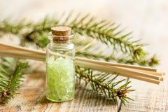Τα μπουκάλια του άλατος και του έλατου θάλασσας διακλαδίζονται για aromatherapy και τη SPA στο ξύλινο επιτραπέζιο υπόβαθρο Στοκ Εικόνες