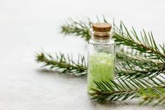 Τα μπουκάλια του άλατος και του έλατου θάλασσας διακλαδίζονται για aromatherapy και τη SPA στο άσπρο επιτραπέζιο υπόβαθρο Στοκ Εικόνες