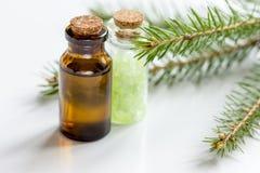 Τα μπουκάλια του ουσιαστικού πετρελαίου και του έλατου διακλαδίζονται για aromatherapy και τη SPA στο άσπρο επιτραπέζιο υπόβαθρο Στοκ εικόνα με δικαίωμα ελεύθερης χρήσης