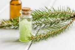 Τα μπουκάλια του ουσιαστικού πετρελαίου και του έλατου διακλαδίζονται για aromatherapy και τη SPA στο άσπρο επιτραπέζιο υπόβαθρο Στοκ φωτογραφία με δικαίωμα ελεύθερης χρήσης