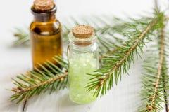 Τα μπουκάλια του ουσιαστικού πετρελαίου και του έλατου διακλαδίζονται για aromatherapy και τη SPA στο άσπρο επιτραπέζιο υπόβαθρο Στοκ φωτογραφίες με δικαίωμα ελεύθερης χρήσης