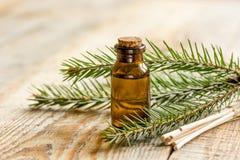 Τα μπουκάλια του ουσιαστικού πετρελαίου και του έλατου διακλαδίζονται για aromatherapy και τη SPA στο ξύλινο επιτραπέζιο υπόβαθρο Στοκ Εικόνες