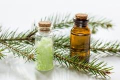 Τα μπουκάλια του ουσιαστικού πετρελαίου και του έλατου διακλαδίζονται για aromatherapy και τη SPA στο άσπρο επιτραπέζιο υπόβαθρο Στοκ Φωτογραφία