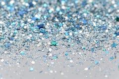 Τα μπλε και ασημένια παγωμένα χειμερινά λαμπιρίζοντας αστέρια χιονιού ακτινοβολούν υπόβαθρο Διακοπές, Χριστούγεννα, νέα αφηρημένη Στοκ Φωτογραφίες